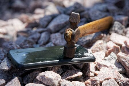 Broken glass of smartphone with hammer on gravel stones. Selective focus.