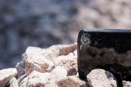 Broken glass of smartphone on granite stones. Selective focus.