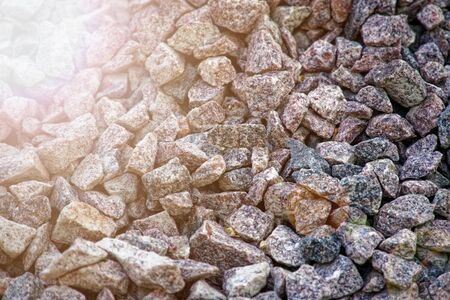 Road gravel and granite gravel texture. Crushed Gravel background. Pile of Stones texture with sunbeam lights. Industrial coals. Reklamní fotografie