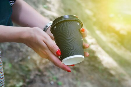 Female hand with black paper cup of coffee take away.