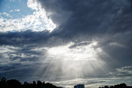 Rays of bright sun peep out from behind dark clouds, sun break after storm. 版權商用圖片