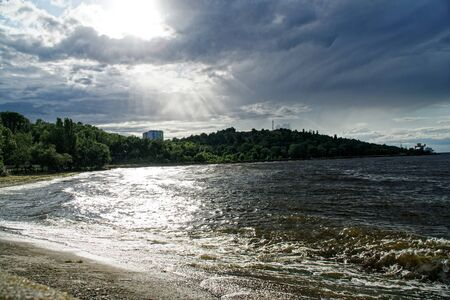 Surging wave on the Kyiv sea reservoir, water reflection, foam and sun beam.