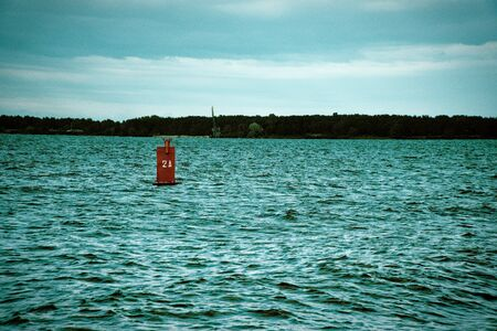 Red buoy drifts in the swell against a blue sky