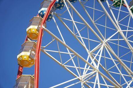 Carrousel. Grande roue sur fond bleu. Voitures de la grande roue.