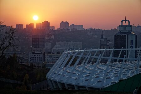 Stadium construction. Aerial view of the stadium roof on the city's background. Sunset behind stadium for soccer. 免版税图像