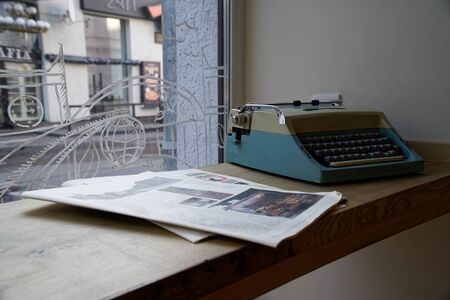Old typewriter in antique photography vintage simulated, grunge photo with newspaper.