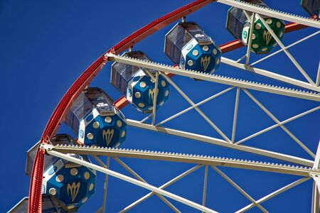 Carousel. Ferris Wheel on a blue background. Carriages of the big wheel. 免版税图像