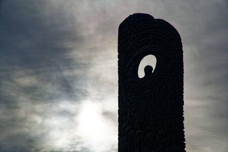 Dark monument with hole against sun and gray sky.