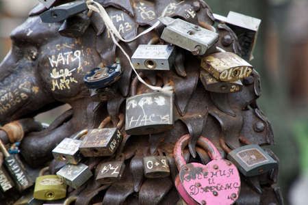 Love padlocks at rusty statue of bronze lion.