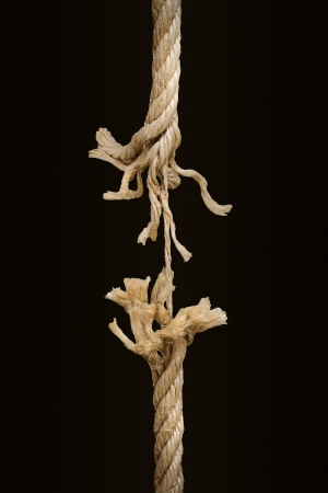 frayed: Close up of a breaking rope over a dark background Stock Photo