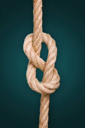 Close up of a knotted rope over a gradient background