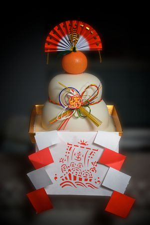 designate: A traditional Japanese new year decoration that is designed to look like a mochi, or rice cake. The paper frills designate it as a holy or sacred object. These items are displayed around Japanese homes over the year year holiday.