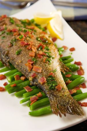 Fried trout with bacon and beans photo