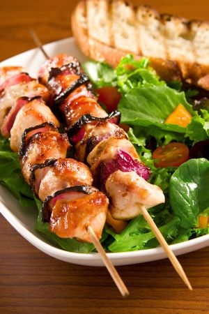 Chicken onion on skewers with salad and crouton