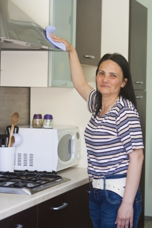 Maid cleaning the kitchen hood with cloth and smiling  photo