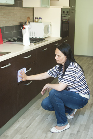 Adult woman kneeling to clean the lower furniture  photo