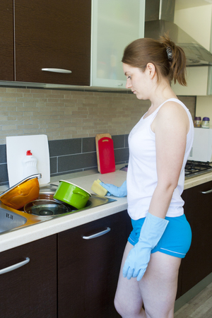 Beautiful young girl looking at the amount of dishes in the sink to be washed  photo