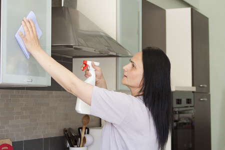 Adult dark haired woman washing the furniture in the kitchen with cloth and spray cleaner  photo