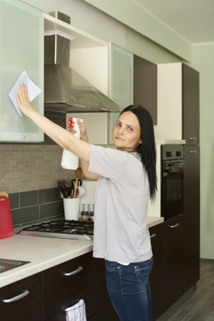 Beautiful young woman in jeans cleaning furniture in kitchen, looking at camera  photo