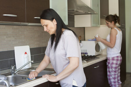 Mother and daughter cleaning in the kitchen  photo