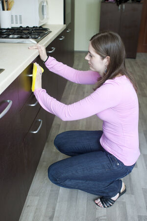 Attractive girl polishing furniture on the kitchen photo