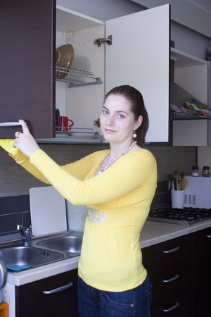 Young girl in yellow blouse polishing furniture on the kitchen photo