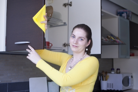 Attractive girl in yellow blouse washing a furniture on the kitchen photo