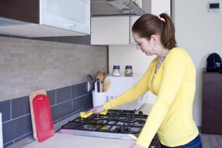 Attractive girl polishing furniture with a spray and towel on the kitchen photo