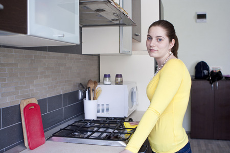 Attractive housewife cleaning the stove on the kitchen photo