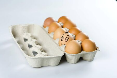 Funny brown egg with smile among others in grey container photo