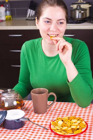Attractive girl sitting at the table and  drinking tea