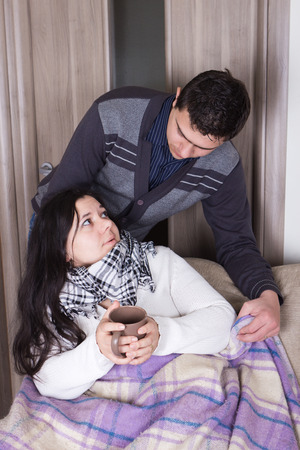 Attentive husband blanketing his wife with flu photo