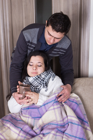 Attentive husband blanketing his wife with flue. photo