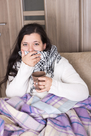 Young girl with flu sitting on couch under blanket and drinking hot tea   photo