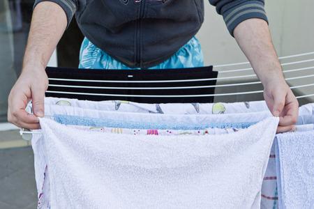 wet clothes: Las manos del hombre colgando la ropa mojada en la ropa-line para el secado Foto de archivo