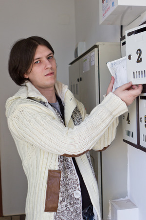 addressee: Young man picking up mail from mailbox Stock Photo