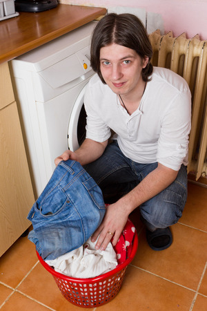 Young man separates clothes before putting it in washing machine photo