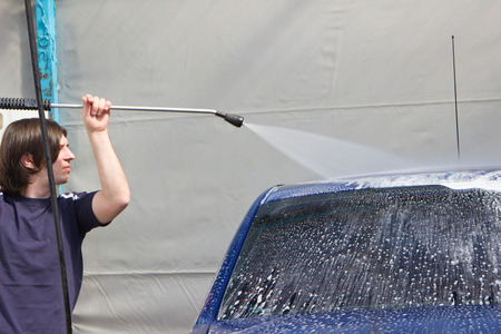 blaster: Young man washing car in carwash with high pressure blaster