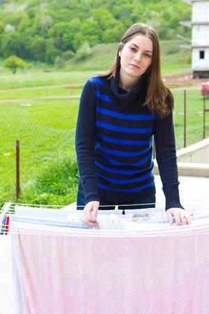 wet clothes: Attrctive chica joven que pone la ropa mojada a secar al aire libre