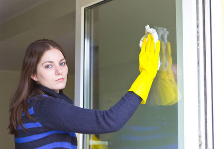 Tired maid with rubber gloves washing windows photo