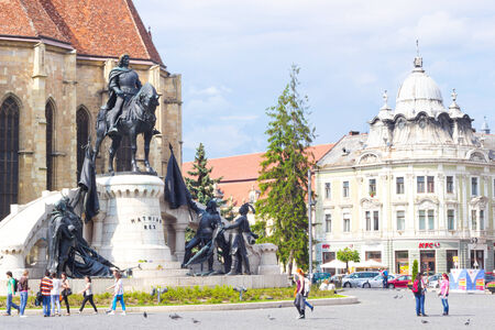 cluj: CLUJ-NAPOCA, ROMANIA - MAY 20, 2014: Piata Unurii (Union Square) with St. Michaels Church and the statue of King of Hungary Matthias Corvinus at sunny day in Transylvania. Editorial