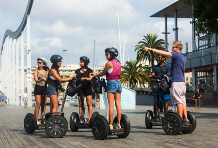 colom: BARCELONA, SPAIN - JULY 6, 2014: Tourists sightseeing on Segway tour of Barcelona, Spain