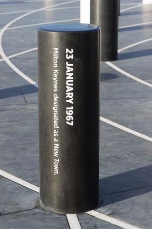 mk: Milton Keynes, Inglaterra - 16 de enero de 2015: El MK Rose, creado por el artista Gordon Young, monumento moderno con los pilares destinados a diferentes acontecimientos hist�ricos y la pir�mide de luz a la distancia en Milton Keynes, Reino Unido