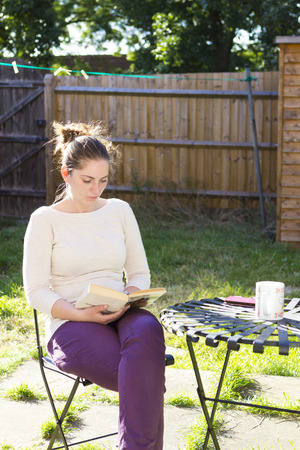 clothes interesting: Young woman sitting in garden and reading a book