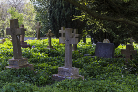 lopsided: MILTON KEYNES, ENGLAND - APRIL 22, 2015: View at Holy Trinity Church churchyard with ancient graves and tombs in Old Wolverton, UK.