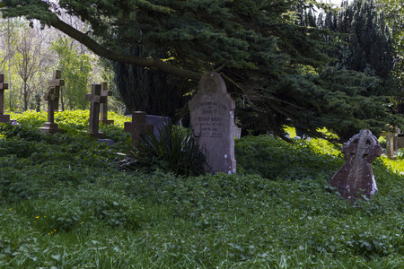 rickety: MILTON KEYNES, ENGLAND - APRIL 22, 2015: View at Holy Trinity Church churchyard with ancient graves and tombs in Old Wolverton, UK.