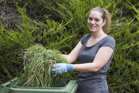 garden waste: Young woman throwing out grass in green bin for garden waste Stock Photo