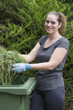 sort out: Young woman throwing out grass in green bin for garden waste Stock Photo