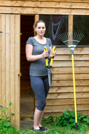horticultural: Portrait of pretty girl with horticultural sundry near backyard shed