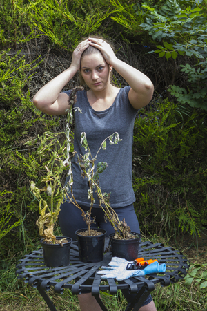 shrunken: Portrait of terrified girl with shrunken plants in backyard